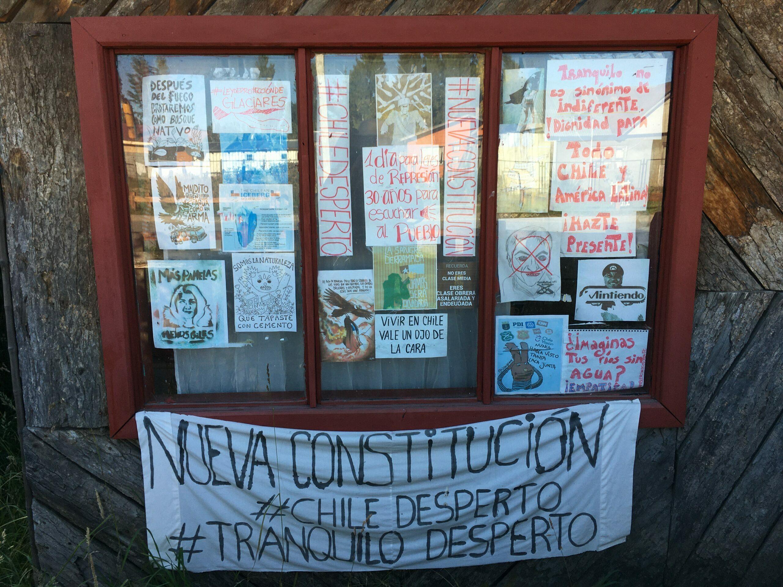 Frontis hogar en la región de Aysén con panfletos alusivos a la revuelta de octubre de 2019